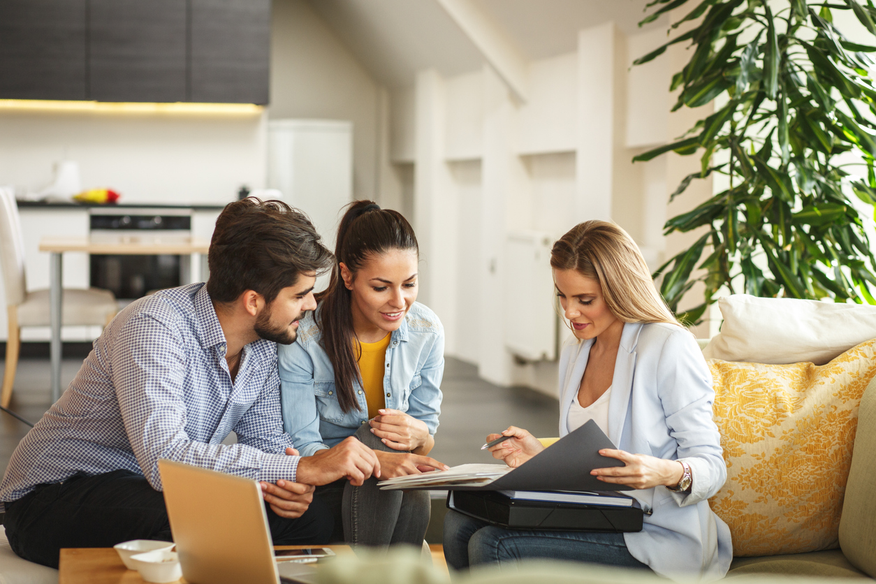 Female Real Estate agent offer home ownership and life insurance to young couple.